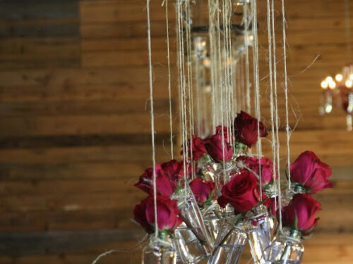 roses in small glass bottles, hanging from barn rafters