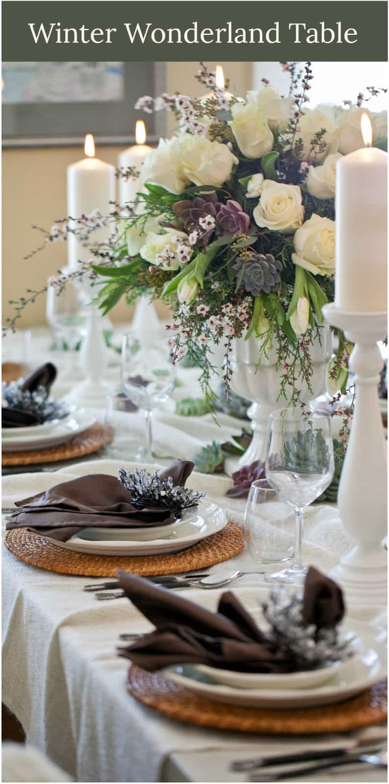 family style table with ivory pillar candles and grande centerpiece in a footed white urn of white roses, tulips, and succulents