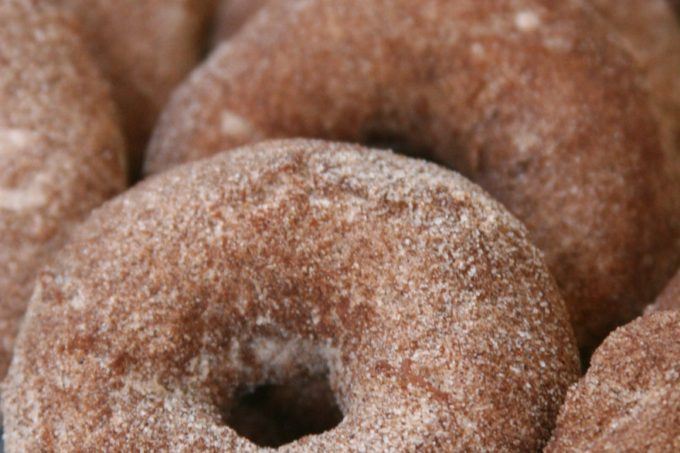 Apple Cider cake doughnuts rolled in cinnamon sugar mixture and lined up against each other on a piece of parchment paper