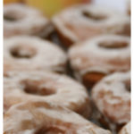 Old Fashioned Doughnuts with an apple cider glaze lined up on a baking rack drying