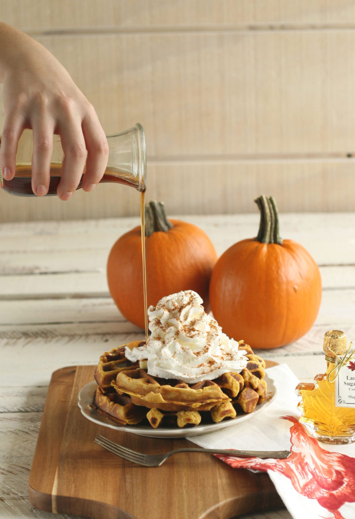 Pumpkin spice waffles on a plate with syrup being board over and whipped cream on top