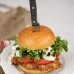 Buttermilk Fried Chicken sandwich on a brioche bun, thick slices of tomato, leaf lettuce, and knife in the center of the bun