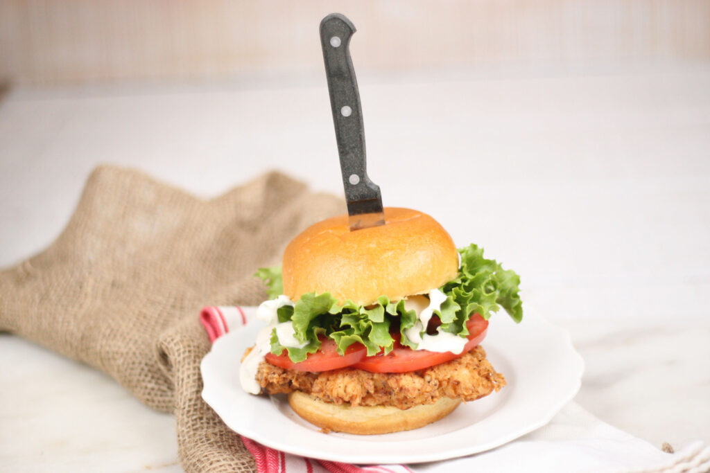 buttermilk fried chicken sandwich with slices of tomatoes, green leaf lettuce and steak knife in the sandwich