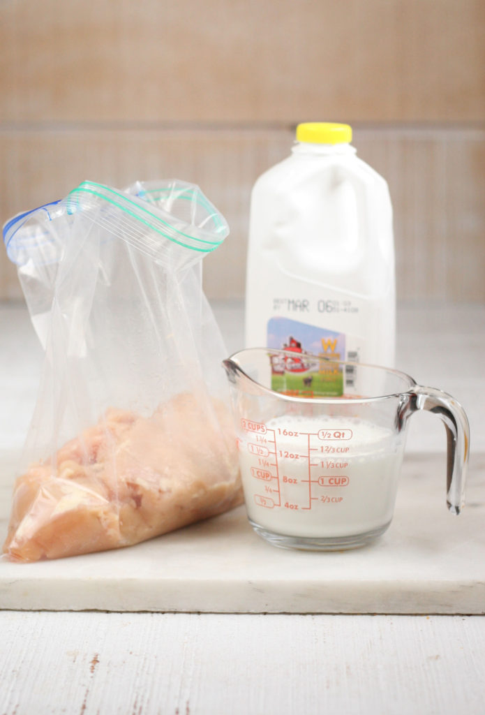 Buttermilk in a glass measuring cup and chicken in a large Ziploc bag