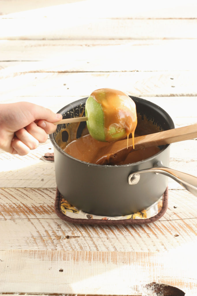 dipping Granny smith apples into hot caramel