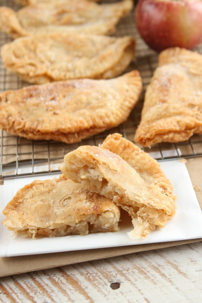 fried apple pies sitting on a baking rack cooling