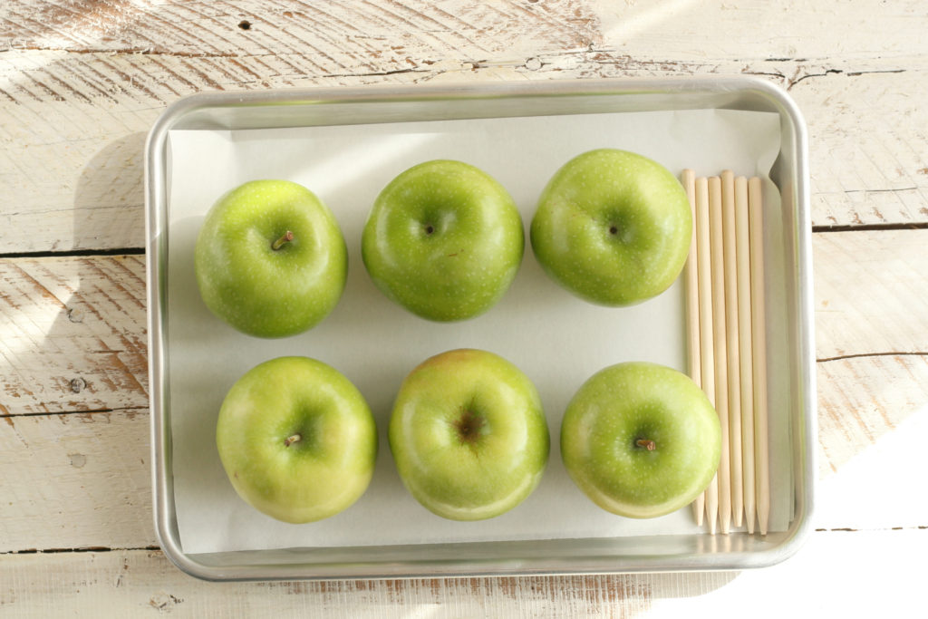 Granny Smith apples with wooden apple sticks sitting on a half sheet pan lined with parchment paper