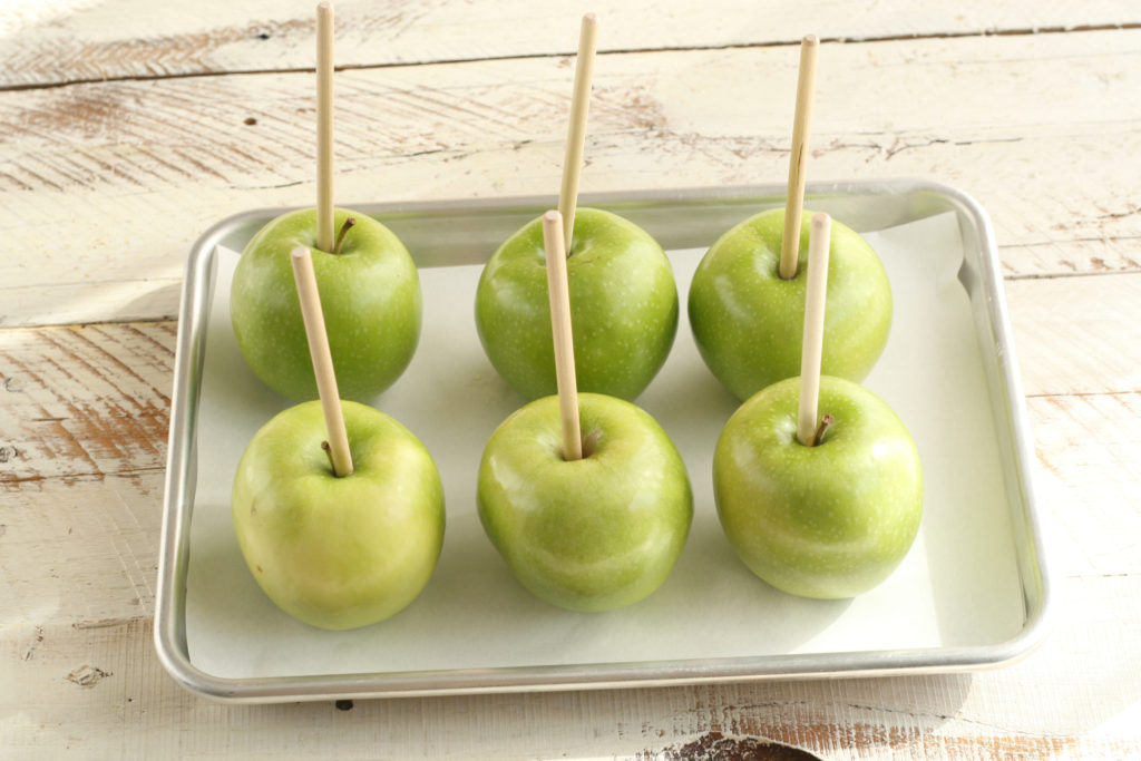 Granny Smith apples with wooden apple sticks sitting on a half sheet pan waiting to be dipped into melted caramel