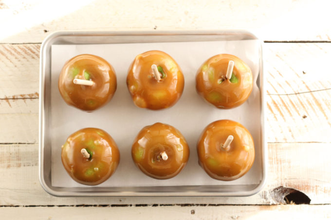 caramel apples cooling on a half sheet pan