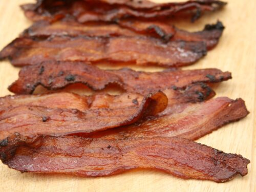 Pieces of maple pepper bacon sitting on wooden cutting board