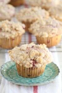 Raspberry Streusel muffin sitting on an aqua floral plate with remainder of muffins cooling in the background on a baking rack.