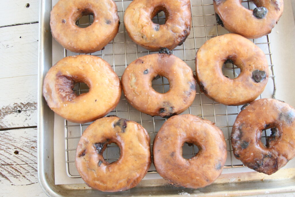 blueberry doughnuts glazed on a baking tray