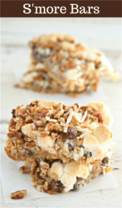 Homemade s'more bars stacked on top of each other with parchment paper