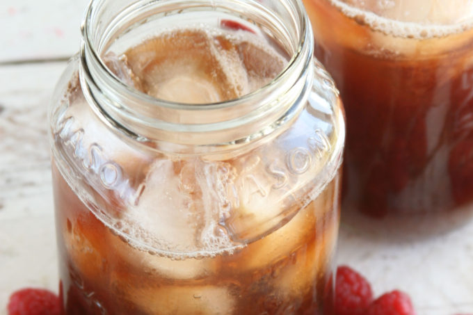 Homemade Raspberry iced tea in glass Mason jars filled with ice cubes