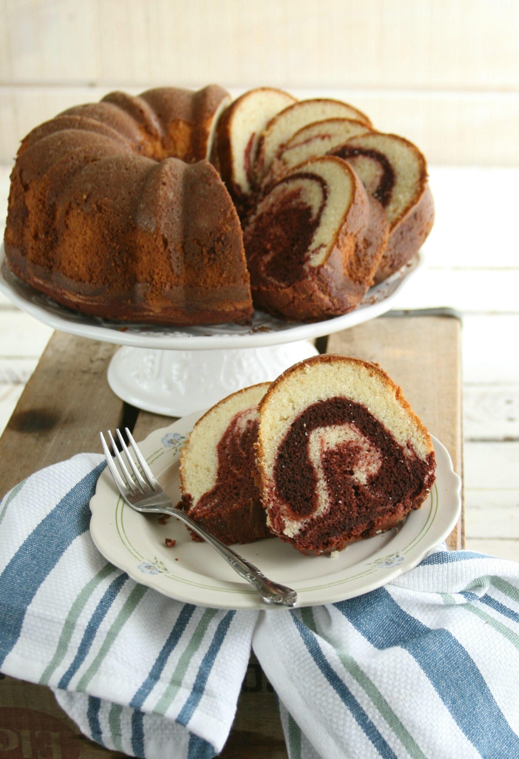 Red velvet marble swirl cake on white footed cake dish.