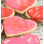 Valentine heart shaped sugar cookies lined up on a baking rack drying