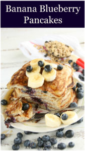 Banana Blueberry pancakes stacked on top of each other on a plate with a fork. Blueberries scattered around and slices of banana on top of the pancakes