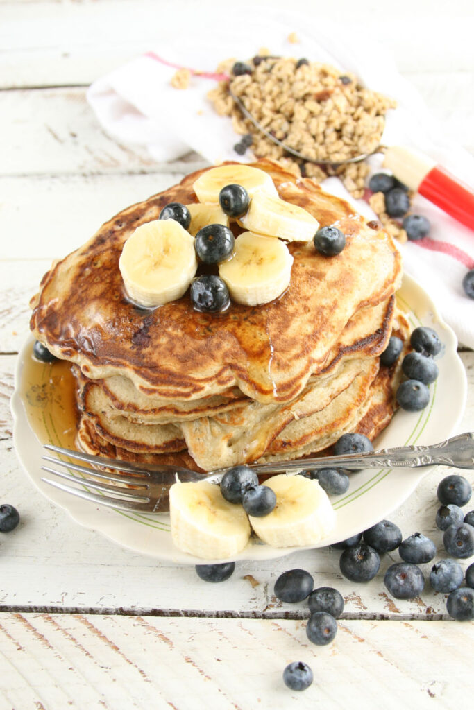 bluberry banana pancakes stacke on plate with maple syrup, fresh banana slices and blueberries