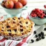 Peach medley pie with weaved crust in a vintage Polish pottery floral pie plate