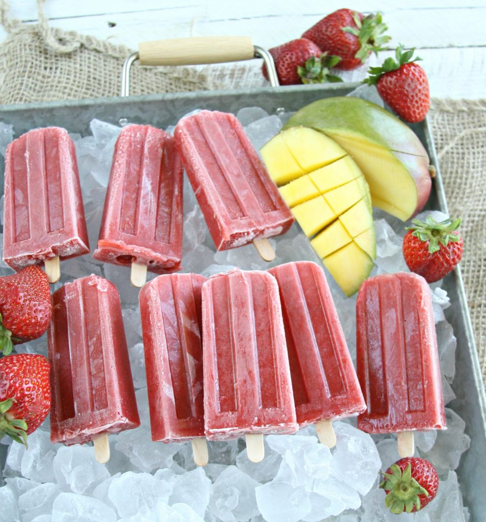 Homemade strawberry mango ice pops sitting in galvanized tray of ice cubes and fresh strawberries surrounding them