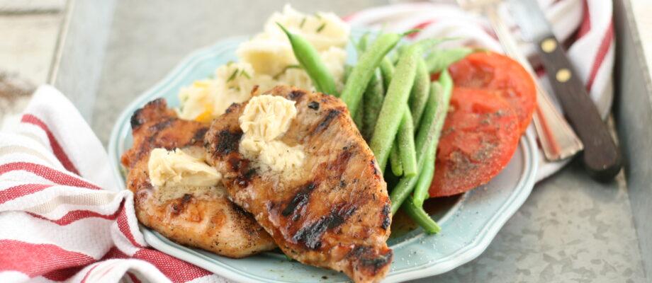 Maple glazed pork chops sitting on light blue plate in galvanized serving tray
