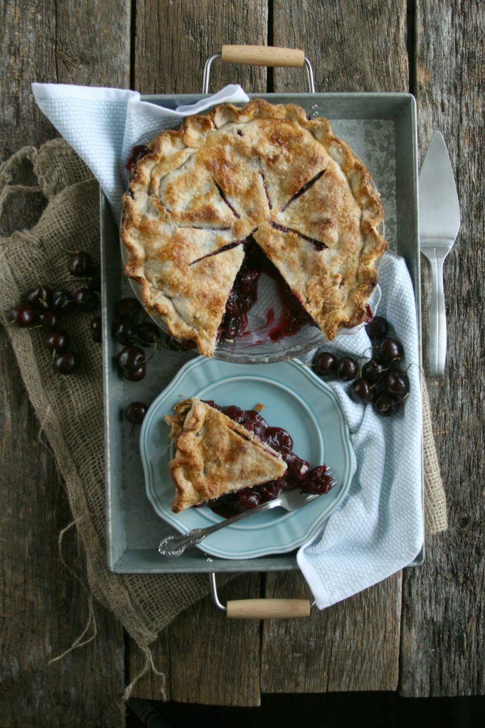 Homemade cherry pie with a slice cut out. Slice of pie sitting on pale blue plate in a galvanized tray.