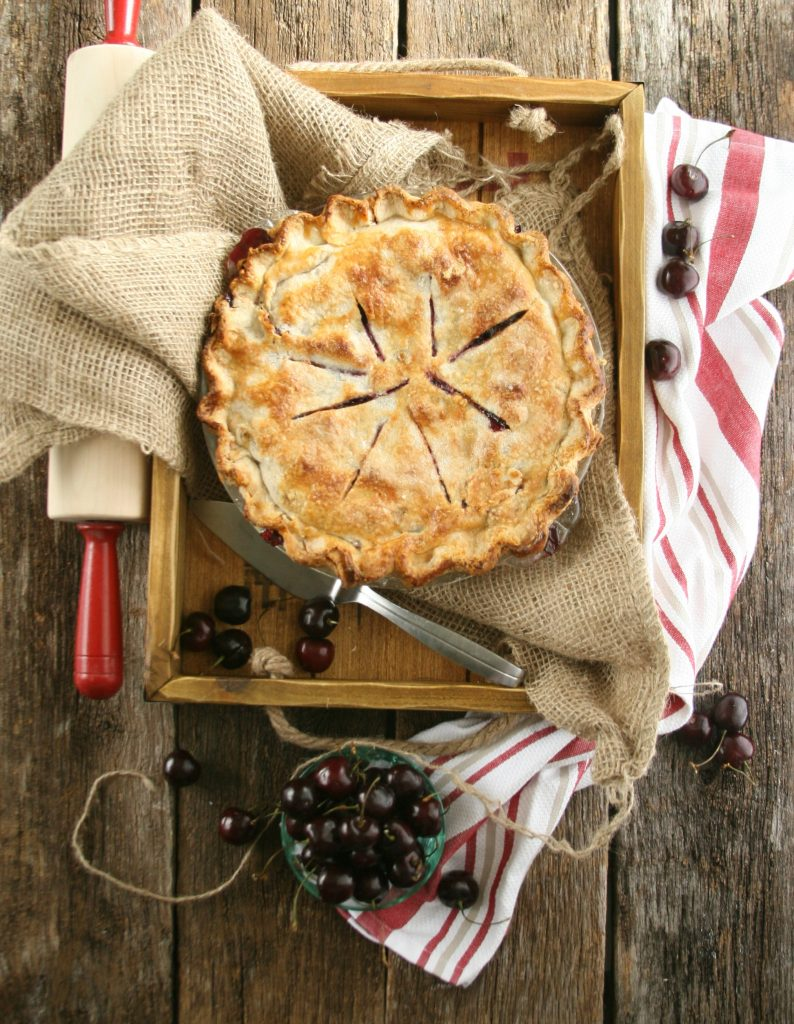 cherry pie with homemade golden color crust sitting in wooden box with burlap and rolling pin with red handles.