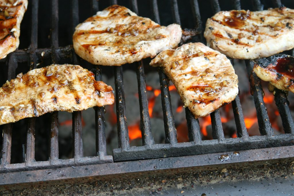 grilled pork chops on the charcoal grill with red hot coals under grates