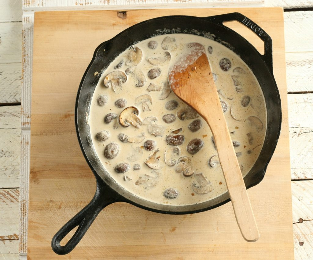 browned mushrooms in a cream sauce in a cast iron skillet