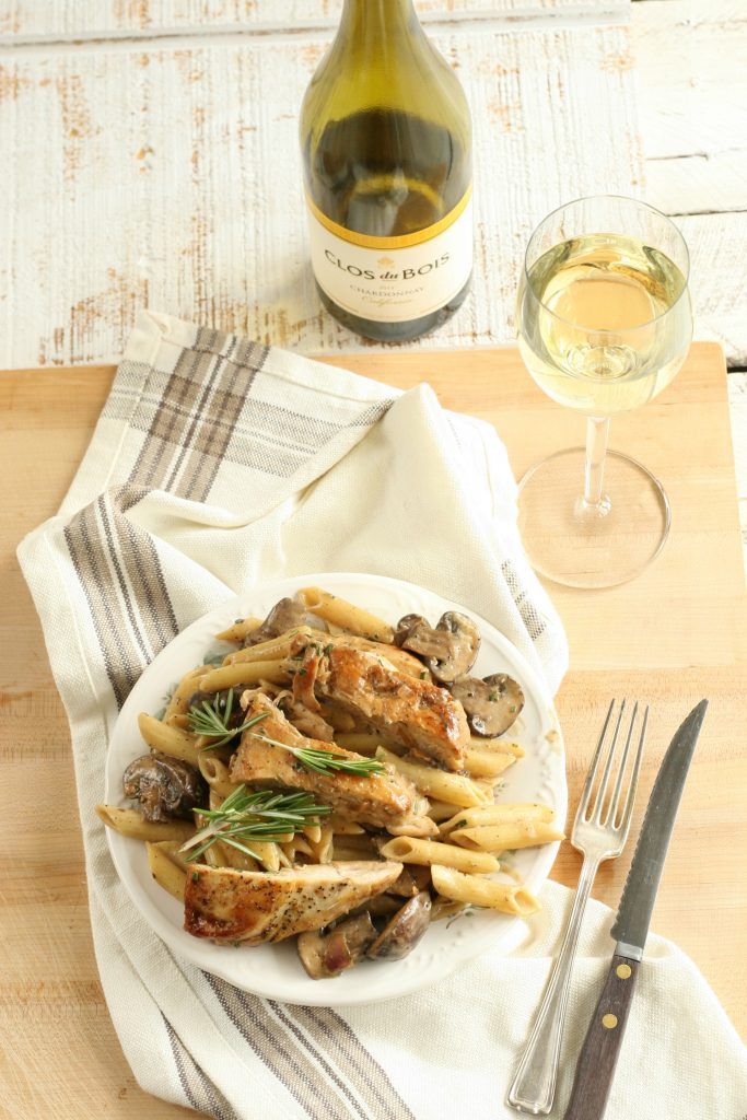 lemon rosemary chicken and pasta on a white plate with cloth napkin, fork and knife