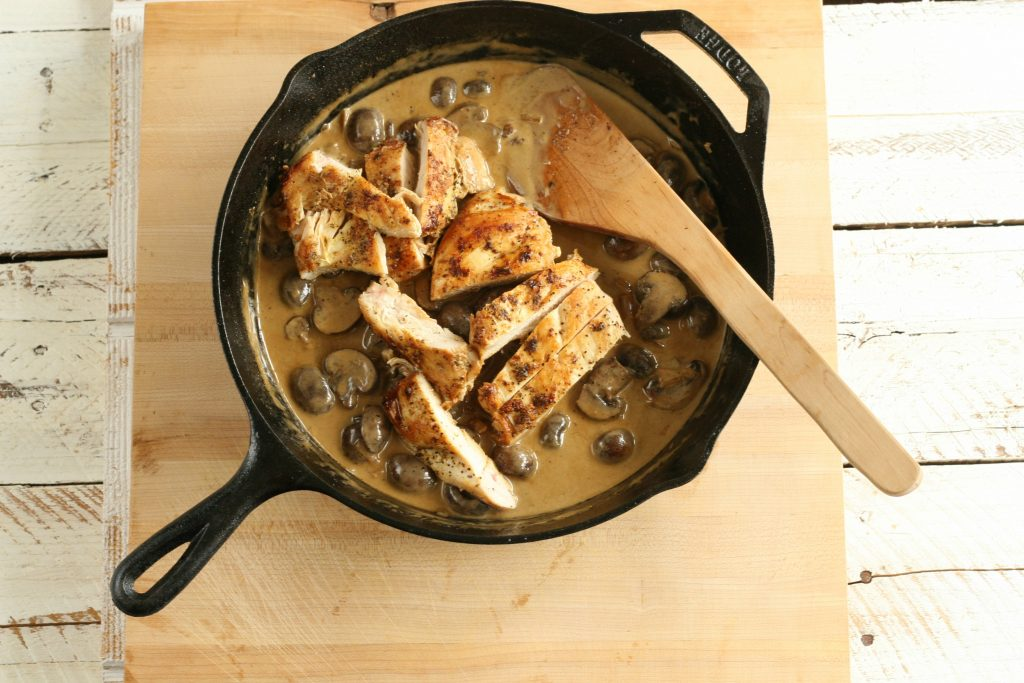 chicken and mushrooms in a cream sauce in a cast iron skillet