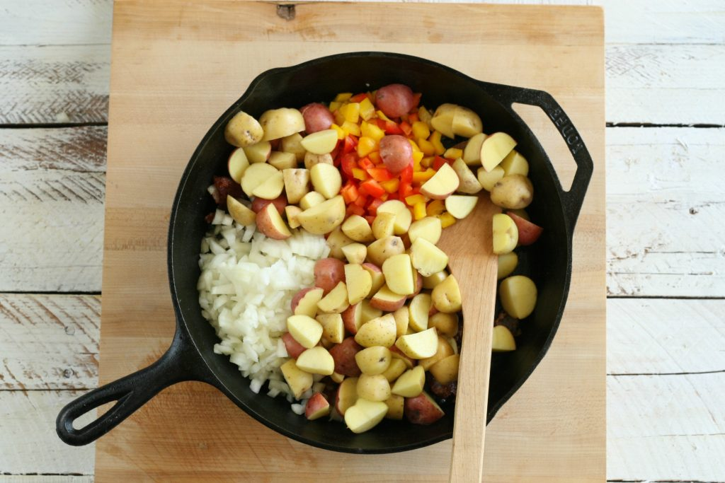 onions, bell peppers, and potatoes in a cast iron skillet