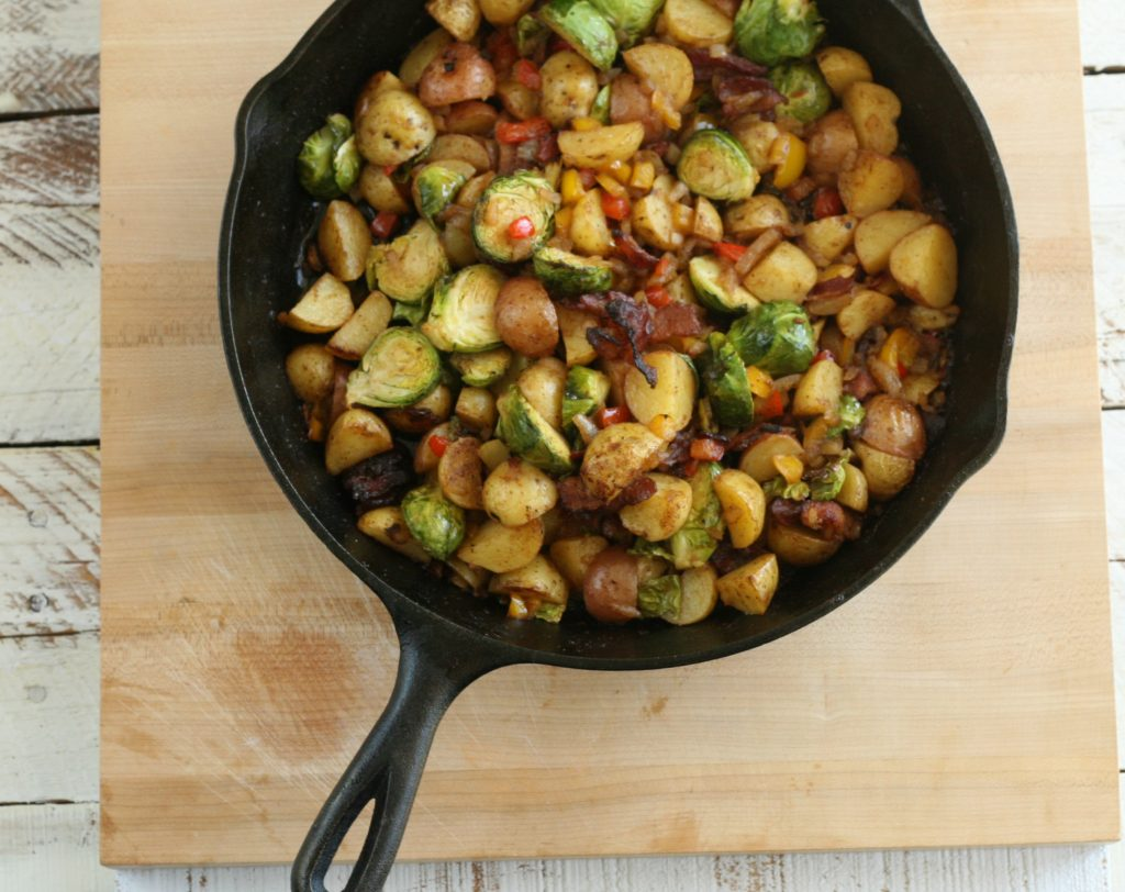 potatoes and brussel sprouts in a cast iron skillet