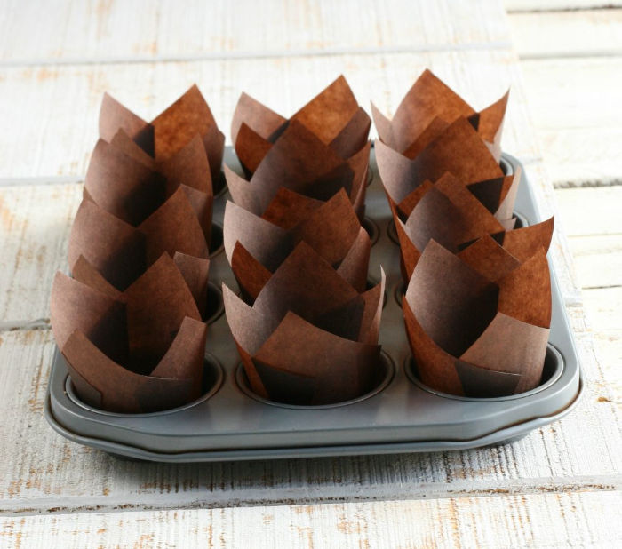 chocolate color tulip shaped paper cupcake liners in a muffin tin