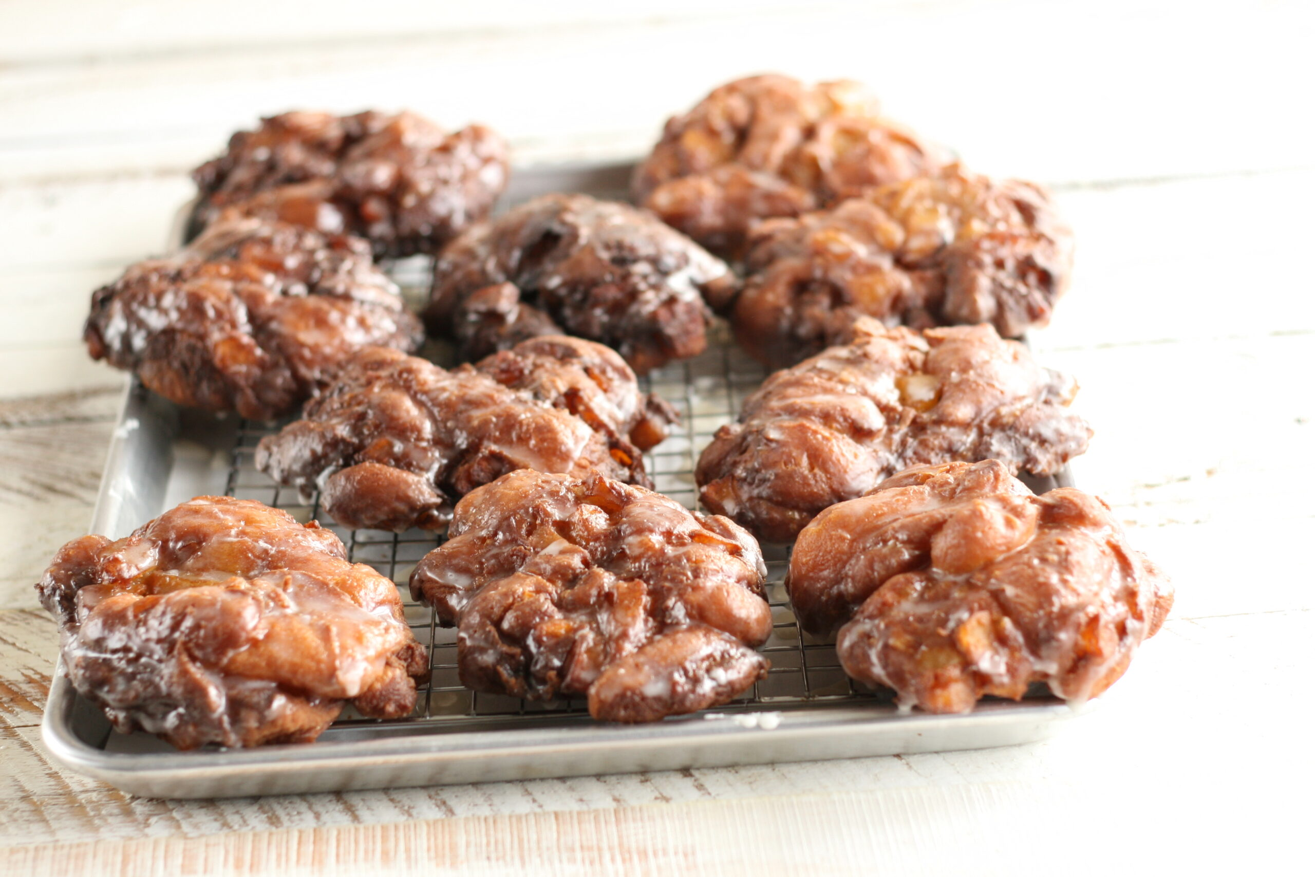 Apple Fritters with a glaze sitting on a sheet pan and baking rack.