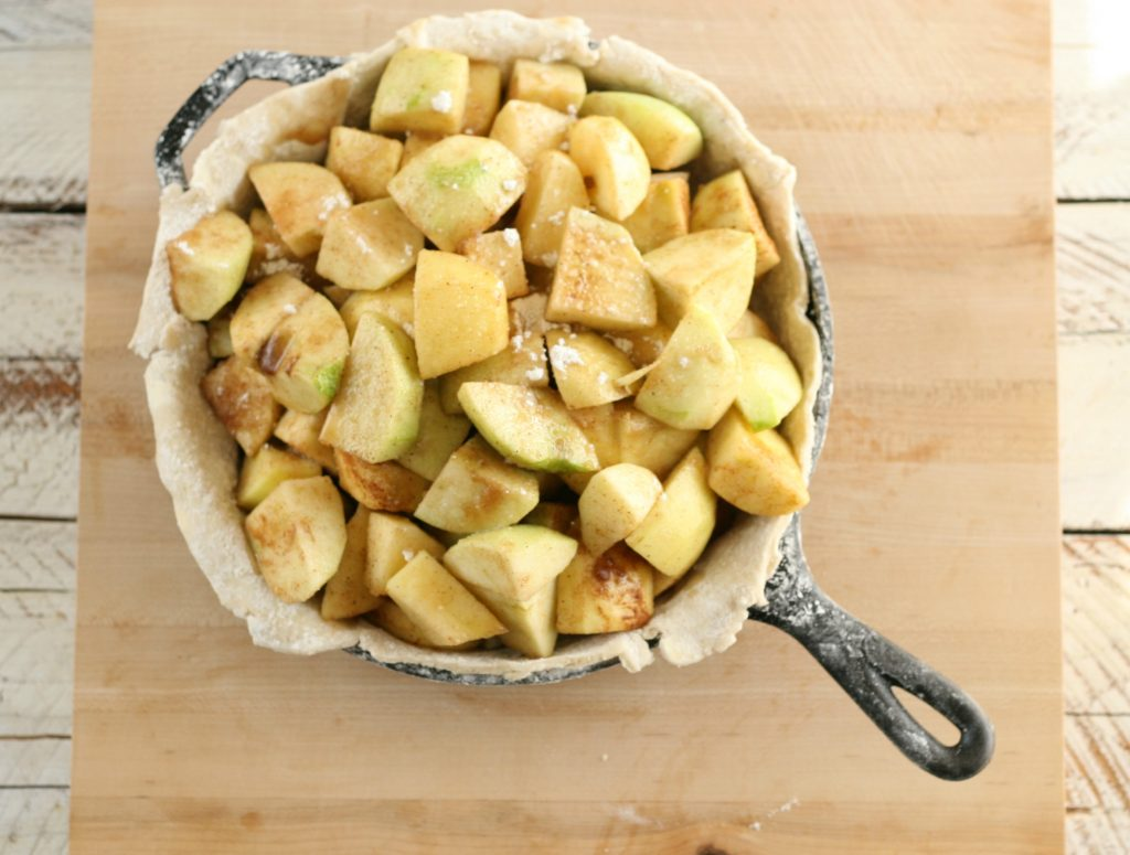 apples piled in a bottom crust in a cast iron skillet