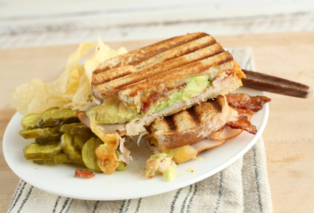 turkey bacon avocado panini on a white plate with potato chips and pickles