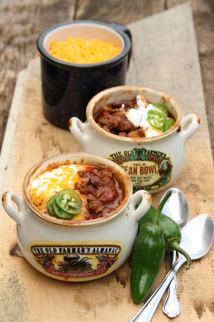 Homemade chili in little crock pots with shredded cheese and pieces of jalapeno peppers