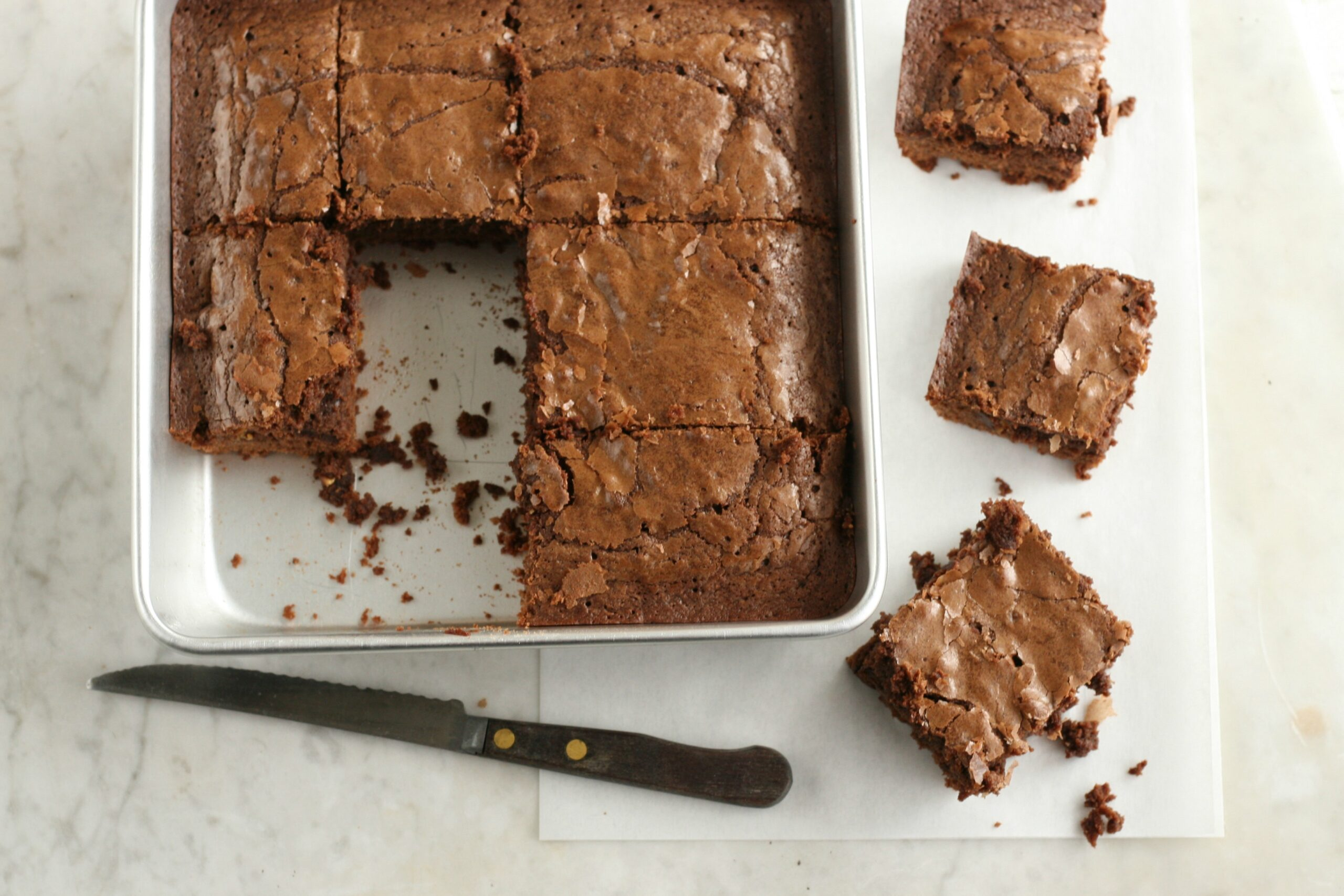 Homemade brownies in square metal baking dish, cut into squares. Some outside the pan to the right.