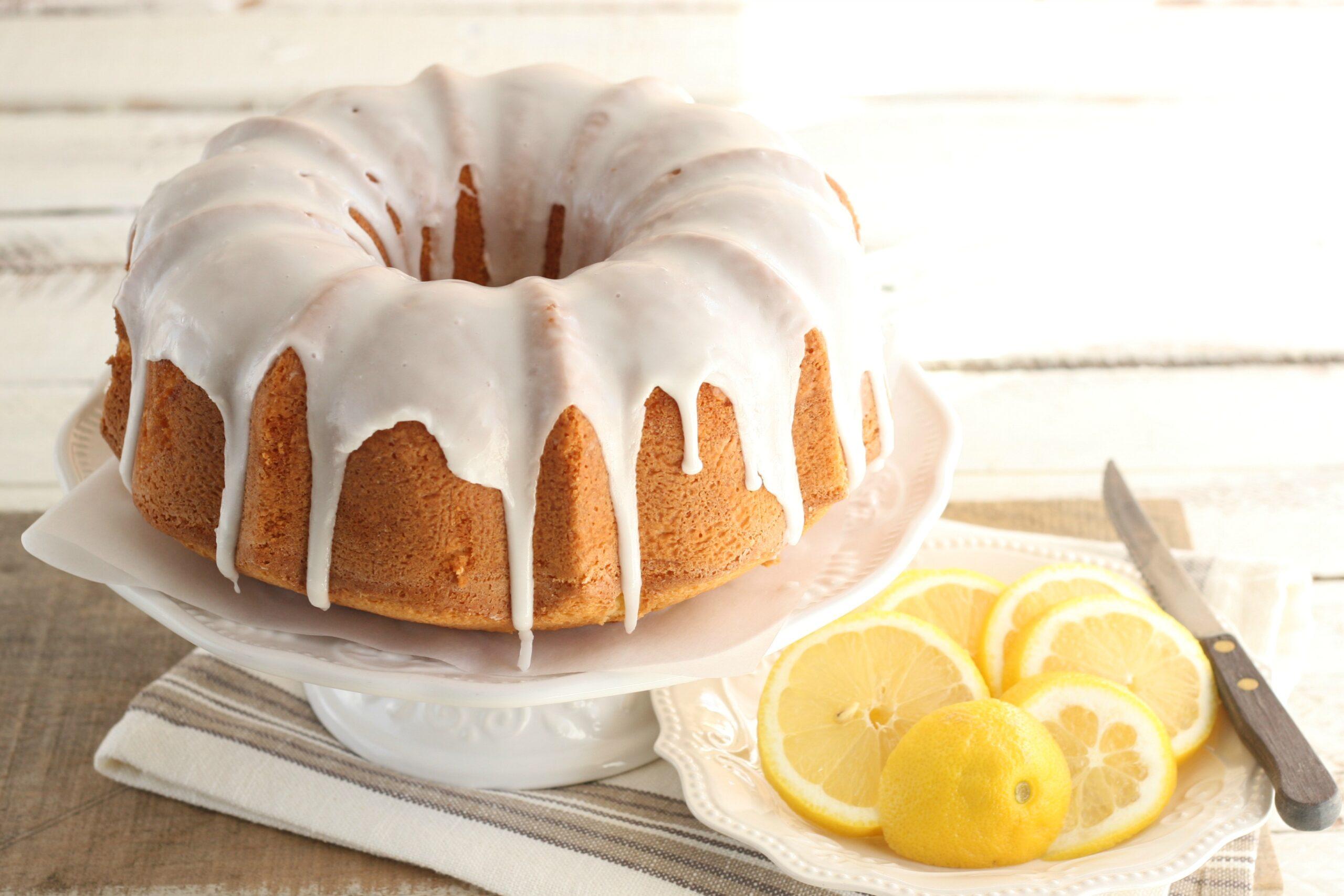 Lemon Bundt cake with icing down sides on white footed cake dish, slices of lemons.