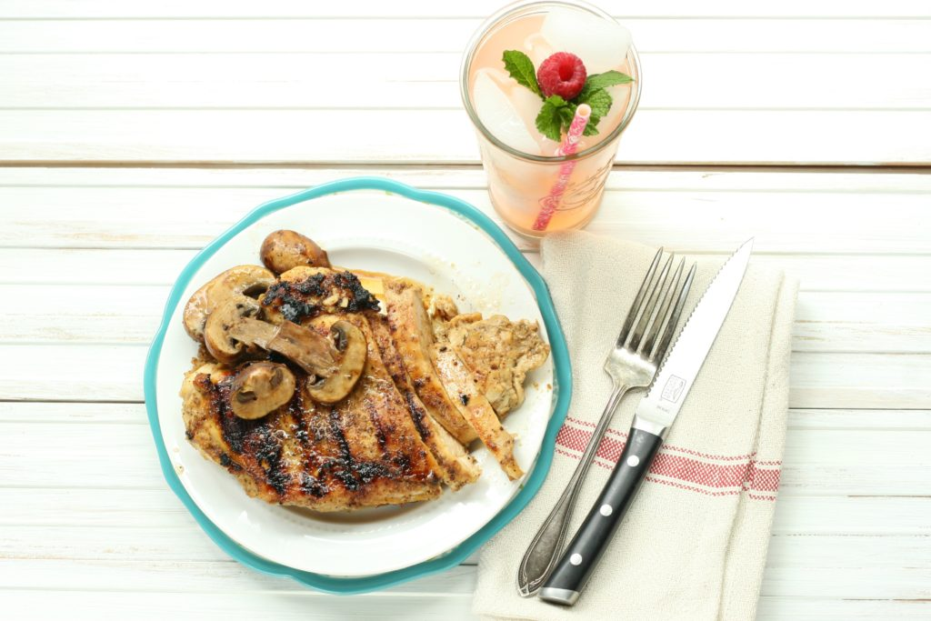 Maple whiskey grilled chicken on a plate with sauteed mushroom and glass of strawberry rhubarb lemonade
