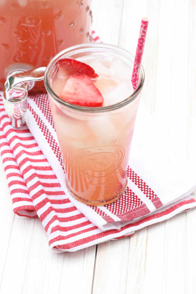 strawberry rhubarb lemonade in a clear glass with slices of strawberries, pink paper straw in the glass