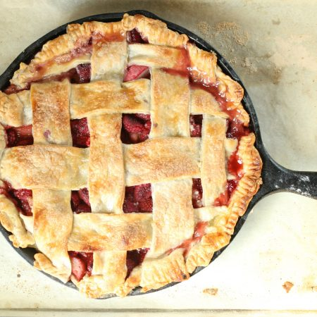 strawberry raspberry rhubarb pie with lattice crust in a cast iron skillet sitting on half sheet pan lined with parchment paper