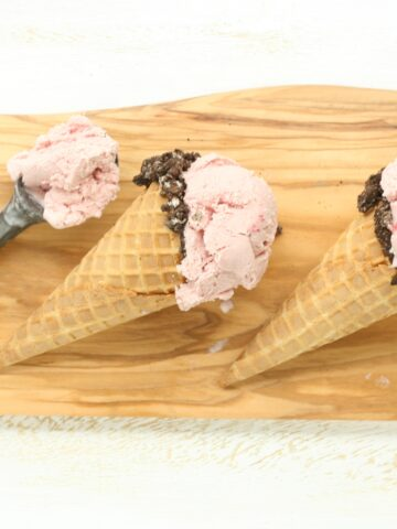 Homemade strawberry ice cream in store bought waffle cones with edges dipped in chocolate and crushed Oreo cookies
