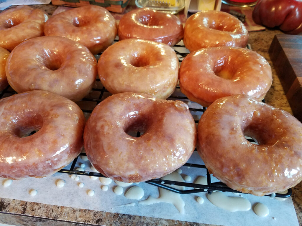 homemade glazed doughnuts on baking rack drying