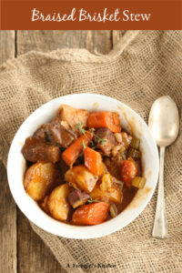 bowl of beef stew with chunks of carrots and potatoes sitting on reclaimed wood and burlap