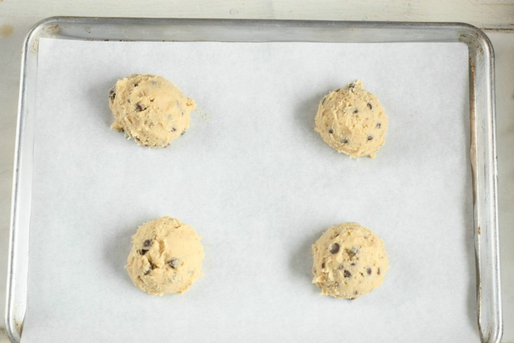 Scoops of chocolate chip cookie dough on a half sheet pan lined with white parchment paper