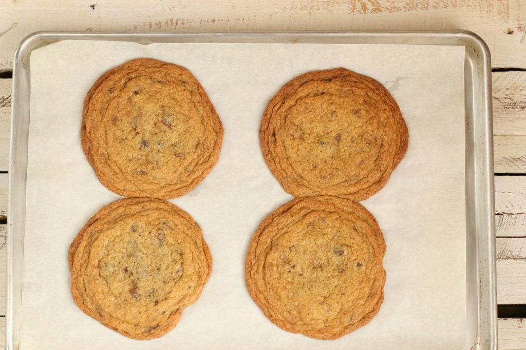 oversized chocolate chip cookies with rippled edges cooling on a half sheet pan lined with parchment paper