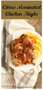 Citrus marinated chicken thighs on a white plate and fork and knife to the left side. Sitting on natural linen and burlap