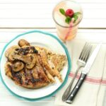 maple whiskey grilled chicken with sauteed mushrooms on a white plate and glass of pink lemonade